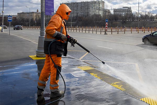 Road worker cleaning city street with high pressure power washer